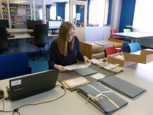 Colour photo of Elizabeth in the Reading Room with folders of papers