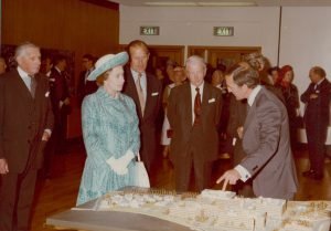 Colour photo of the Queen, surrounded by middle-aged men in suits, looking at the model cake on the table