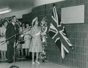 Black and white photo of the Queen removing the Union Jack curtain cover in the plaque