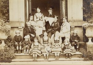 Family photo posed on steps between two columns, with adults at the back and children sitting on the steps in the front