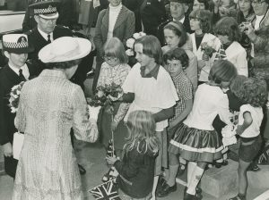 Black and white photo of the Queen being handed flowers by children