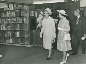 Black and white photo of the Queen, accompanied by an older lady, walking past shelves of boo