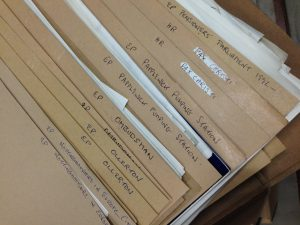 Close up of brown card files with labelled in biro