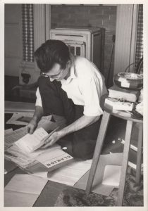 Black and white photo of Ken Coates crouching over papers strewn on the floor, editing Clarion magazine