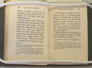 Open pages of the book held by weights, text discussing angels taking the souls of sick children
