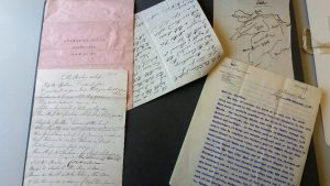 Handwritten and typed letters scattered across the table