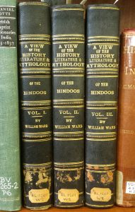Three black and gold bound volumes on the shelf