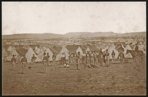 Rows and rows of tents in a rocky, barren landscape, with soldiers in uniform standing and on horseback in the foreground