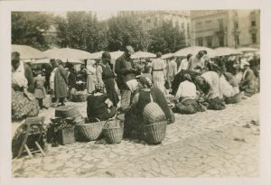 Women bending over to inspect baskets lined up on the market square