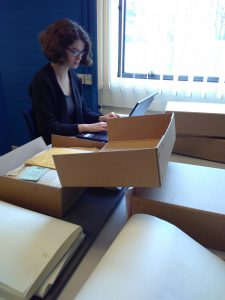 Photo of the volunteer working on a laptop and archive boxes in the Reading Room