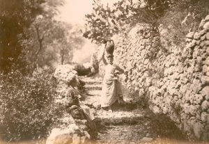 Two women carrying jugs on their heads