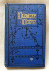 Front cover of the book Janeways Token, the title edged in gold on a royal blue cover with a black embossed vine decoration