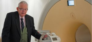 An elderly Mansfield, dressed in a suit, standing next to a modern MRI