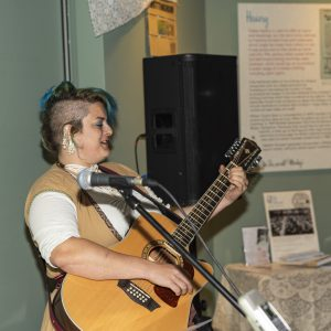 Pixie Styx playing a guitar in the exhibition gallery