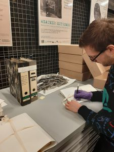 Male library assistant writing on archival paper with a pencil wearing latex-free gloves with old discarded packaging and new archival boxes piled in the background.