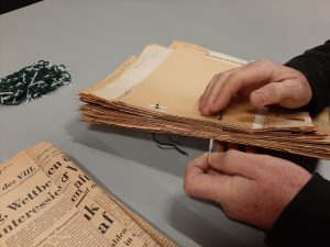 Close up of male hands threading a treasury tag through papers with news cuttings glued to them.