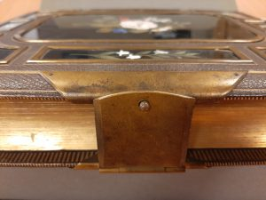 Close up of a simple metal clasp and gold fore-edges of the photo album