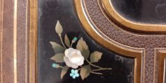 Close up of a black enamel panel with white and blue flowers set into the cover of a photo album