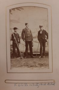 Image of three young men holding walking sticks posing against a backdrop of hills