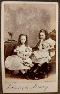 Carte de visitie showing two girls seated holding a doll and a book, labelled Louise and Mary