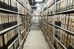 The BMGB in the Store before the work started showing rows of lever arch files on metal shelves