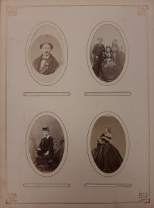 Page from a photo album showing four portrait p photos of unidentified people