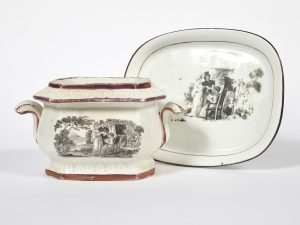 White china sugar bowl and tea plate with a black image depicting Charlotte and Leopold giving a Bible to an elderly woman