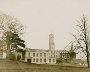 Photograph of the Trent Building most of the way through construction, there is a crane and some slabs of stone to one side