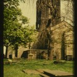 Colour photo of the church tower in summer, with graves in the foreground.