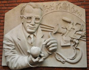 Frieze of Woody Allen holding an apple next to a TV camera, made of lightweight resin but meant to look like stone