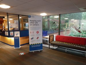 The reception area with safety measures including hand sanitiser station, signage and taped off chairs