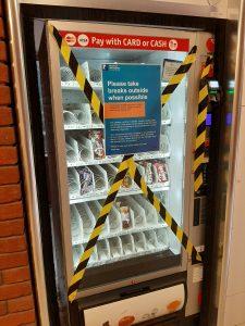Vending machine covered in hazard tape.