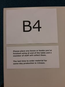 Table number stuck to the table with a note about document production procedures