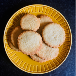 Photo of a plate of round biscuits with fluted edges, on a yellow plate on a dark kitchen counter