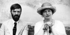 Black and white photo of Lawrence, wearing a light suit and tie, and Frieda, wearing a sunhat and grasping a walking stick, shown from the waist up, looking at the camera without expression
