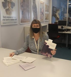 Woman wearing a face mask sitting at a desk with unbound chapters from the book in a box novel The Unfortunates in front of her and in her hands