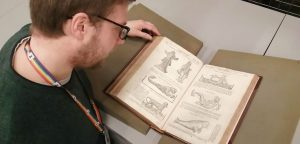 Man photographed from above, looking at a book open at etchings of fantastical beasts