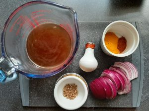 Spices and gravy for the curry arranged in ramekins on a chopping board