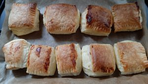 Partially cooked cheese rolls on a baking tray