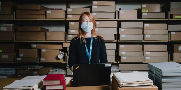Young woman wearing a mask looking at the camera, standing in front of shelves of archive boxes, next to a table on which is a laptop, archive documents and books.
