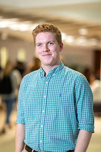 Callum McIntyre in a blue checked shirt smiling at the camera