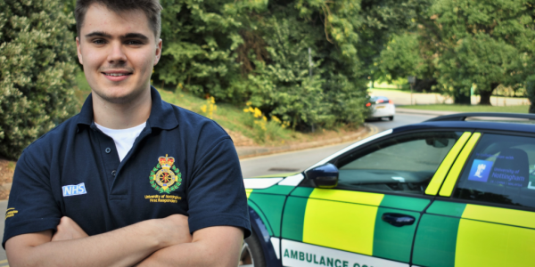 James Conlan smiling at the camera next to a community ambulance