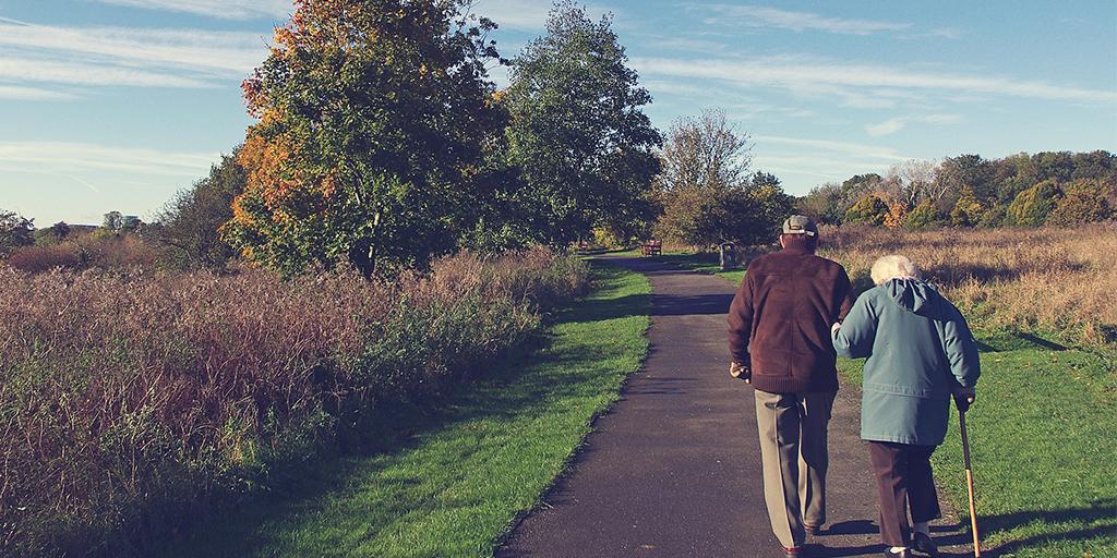 An elderly couple walking along a rural path