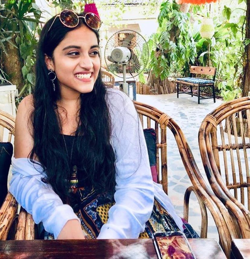 Sanjana Mamidapli smiling in a wicker chair