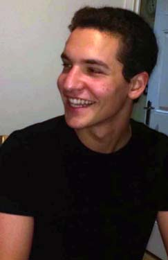 Roei in a black t-shirt smiling at a person out of view of the camera
