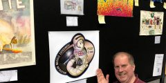 Professor Nate Szewczyk gesturing towards a drawn Worms in Space patch on a wall of artwork