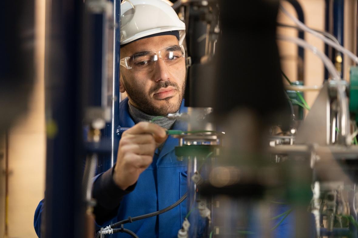 Technician working on a Batch Distillation Column rig