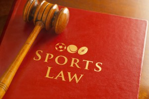 The Law with respect to legal issues in sport, including contractual, corporate, data, media, disputes, events, intellectual property, marketing, regulatory, representation, management and agents, etc. A red leather law book with a judges gavel and Sports Law with gold embossed text and symbol.