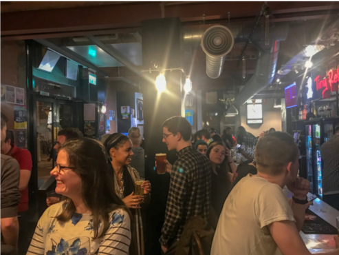 crowded bar with people smiling and drinking