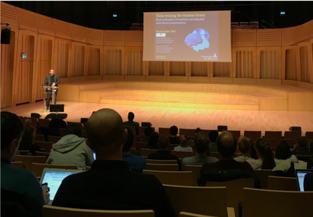 view from lecture theatre audience of man at podium with projection behind of slide with image of a human brain